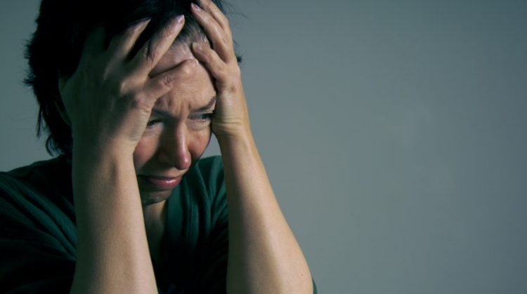 A woman is sad/troubled/depressed. Many emotions can be read into this image.